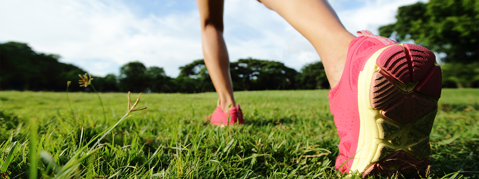 Runner in pink trainers on green field